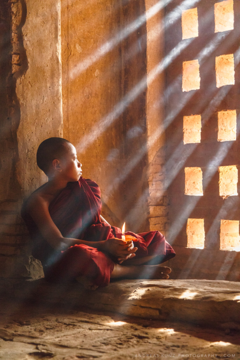 Monk candle sun rays in temple